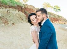 Bruid en bruidegom bij huwelijksceremonie dichtbij overzees door de zonsondergang stock foto's