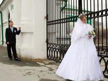 Bruid en bruidegom bij poort Stock Foto's