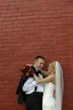 Bruid en Bruidegom bij rode bakstenen muur Stock Foto