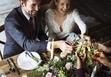 Bruid en Bruidegom Clinging Wineglasses met Vrienden op Ontvangst stock afbeelding
