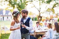 Bruid en bruidegom clinking glazen bij huwelijksontvangst buiten in de binnenplaats stock afbeelding
