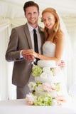Bruid en Bruidegom Cutting Wedding Cake bij Ontvangst Stock Foto's