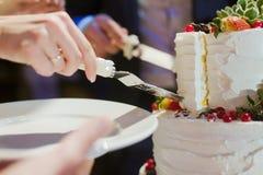 Bruid en bruidegom de cake van het besnoeiingshuwelijk Stock Foto