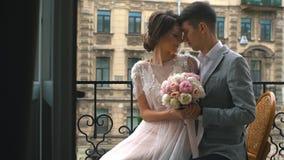 Bruid en bruidegom de kus die zich op de oude steenbalkon, Jonge, mooie paarbruidegom bevinden en de bruid bevindt zich op balkon stock video