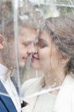 Bruid en bruidegom in de regen terwijl het glimlachen en het kijken aan elkaar Royalty-vrije Stock Foto