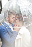 Bruid en bruidegom in de regen terwijl het glimlachen en het kijken aan elkaar Stock Afbeeldingen