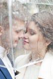 Bruid en bruidegom in de regen terwijl het glimlachen en het kijken aan elkaar Royalty-vrije Stock Fotografie