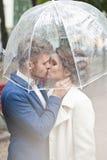 Bruid en bruidegom in de regen terwijl het glimlachen en het kijken aan elkaar Royalty-vrije Stock Foto's