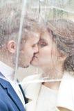 Bruid en bruidegom in de regen terwijl het glimlachen en het kijken aan elkaar Royalty-vrije Stock Afbeelding