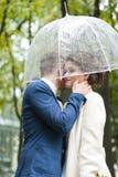 Bruid en bruidegom in de regen terwijl het glimlachen en het kijken aan elkaar Stock Afbeelding