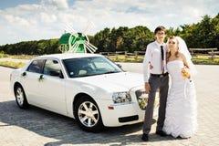 Bruid en bruidegom dichtbij auto Stock Afbeelding