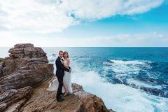 Bruid en bruidegom dichtbij de oceaan Stock Afbeeldingen
