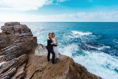 Bruid en bruidegom dichtbij de oceaan royalty-vrije stock fotografie