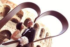 Bruid en bruidegom dichtbij hart gevormd beeldhouwwerk Stock Afbeeldingen