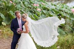 Bruid en bruidegom dichtbij lotosvijver Stock Foto's