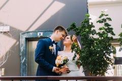 Bruid en bruidegom die aan elkaar kijken Hotelhal die met uitheemse gewassen als achtergrond wordt verfraaid Stock Fotografie