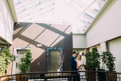 Bruid en bruidegom die aan elkaar kijken Hotelhal met diverse uitheemse gewassen als achtergrond wordt verfraaid die Royalty-vrije Stock Afbeelding