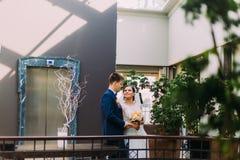 Bruid en bruidegom die aan elkaar met hotelhal als achtergrond kijken Stock Afbeeldingen