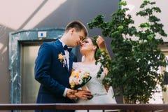 Bruid en bruidegom die aan elkaar vóór de kus met hotelhal als achtergrond kijken Stock Foto's