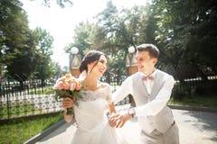 Bruid en bruidegom die bij huwelijksdag in een mooi park, het glimlachen eind lopen die van elkaar genieten royalty-vrije stock fotografie