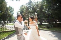 Bruid en bruidegom die bij huwelijksdag in een mooi park, het glimlachen eind lopen die van elkaar genieten stock foto