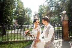 Bruid en bruidegom die bij huwelijksdag in een mooi park, het glimlachen eind lopen die van elkaar genieten stock foto's