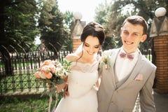 Bruid en bruidegom die bij huwelijksdag in een mooi park lopen, die van elkaar genieten stock foto