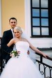 Bruid en bruidegom die bij huwelijksdag in openlucht op de lente dichtbij c koesteren Royalty-vrije Stock Foto's