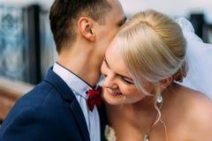 Bruid en bruidegom die bij huwelijksdag in openlucht op de lenteaard koesteren Stock Afbeelding