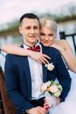 Bruid en bruidegom die bij huwelijksdag in openlucht op de lenteaard koesteren Royalty-vrije Stock Foto
