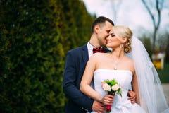 Bruid en bruidegom die bij huwelijksdag in openlucht op de lenteaard koesteren Royalty-vrije Stock Afbeelding