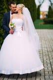 Bruid en bruidegom die bij huwelijksdag in openlucht op de lenteaard koesteren Stock Foto