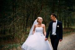 Bruid en bruidegom die bij huwelijksdag in openlucht op de lenteaard koesteren Royalty-vrije Stock Foto's