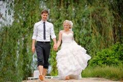 Bruid en bruidegom die blootvoets op het strand lopen Stock Foto's