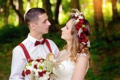 Bruid en bruidegom die in bos lopen royalty-vrije stock afbeelding