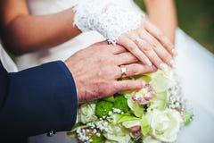 Bruid en bruidegom die bruids boeket dicht tegenhouden Stock Foto's