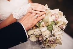 Bruid en bruidegom die bruids boeket dicht tegenhouden Royalty-vrije Stock Foto