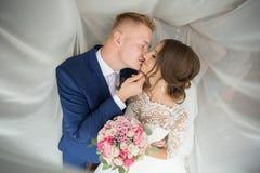 Bruid en bruidegom die bruids boeket houden Stock Foto's