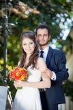Bruid en bruidegom die de camera bekijken Stock Foto