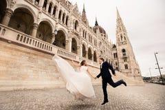 Bruid en bruidegom die in de oude stadsstraat koesteren De gangen van het huwelijkspaar in Boedapest dichtbij het Parlement Huis stock foto's