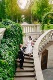 Bruid en bruidegom die in de zomerpark in openlucht lopen met architectuur stock afbeeldingen