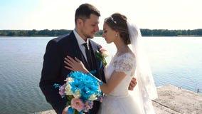 Bruid en bruidegom die dichtbij de handen van de rivierholding lopen Langzame Motie stock videobeelden