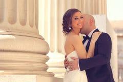 Bruid en bruidegom die dichtbij kolommen omhelzen Royalty-vrije Stock Afbeelding
