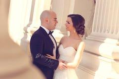 Bruid en bruidegom die dichtbij kolommen omhelzen Stock Foto