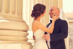 Bruid en bruidegom die dichtbij kolommen omhelzen Royalty-vrije Stock Foto