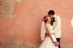 Bruid en bruidegom die dichtbij muur omhelzen Royalty-vrije Stock Afbeeldingen