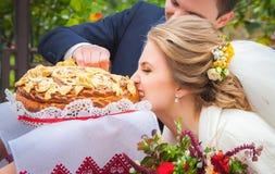 Bruid en bruidegom die door ouders met brood worden ontmoet royalty-vrije stock afbeeldingen