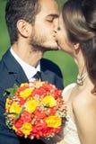 Bruid en bruidegom die elkaar buiten kussen Stock Foto