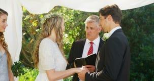 Bruid en bruidegom die gelukkig ringen ruilen terwijl zegen door de priester 4K 4k stock video