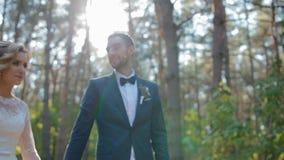 Bruid en bruidegom die in het hout lopen stock videobeelden